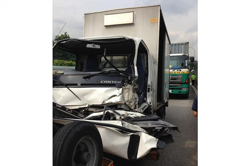 The white lorry that was behind the green lorry. The passenger, in his 20s, was trapped in the vehicle, and was later conveyed to the National University Hospital. The driver, Mr Loo Cheng Kan, was not injured.--ST PHOTO: YE0 SAM JO