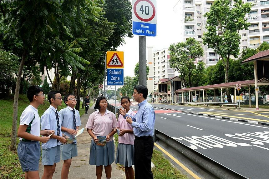 Parliamentary Secretary for Transport, Associate Prof Muhammad Faishal Ibrahim viewing thenewly implemented road safety initiativeswith Shuqun Primary School students on Thursday, Nov 14, 2013. -- ST PHOTO:AZIZ HUSSIN