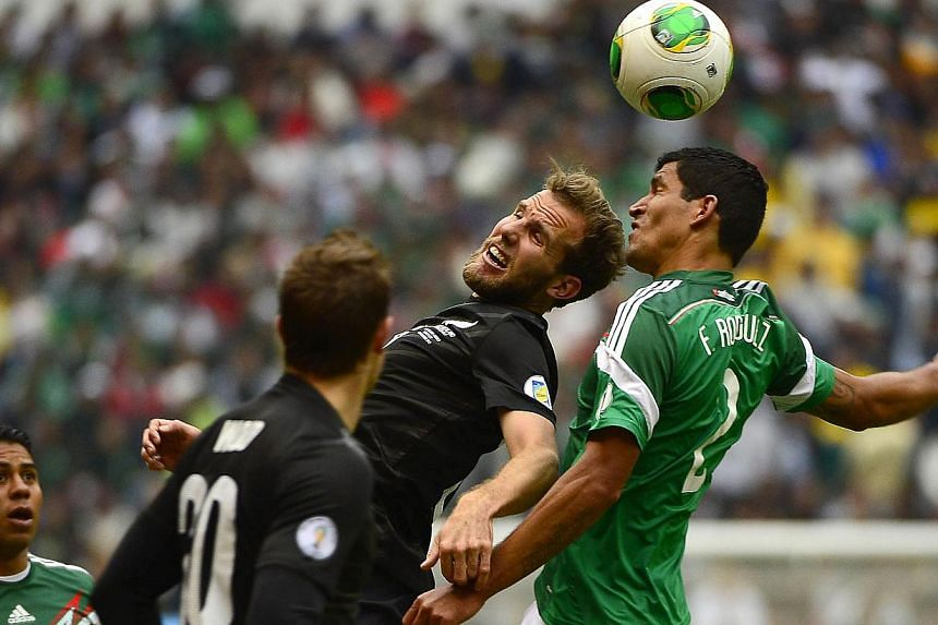 Mexican midfielder Francisco Rodriguez(right) vies with New Zealanders Chris Wood(left) and Jeremy Brockie during their FIFA World Cup intercontinental play-offs match at the Estadio Azteca in Mexico on November 13, 2013. With a resounding victo