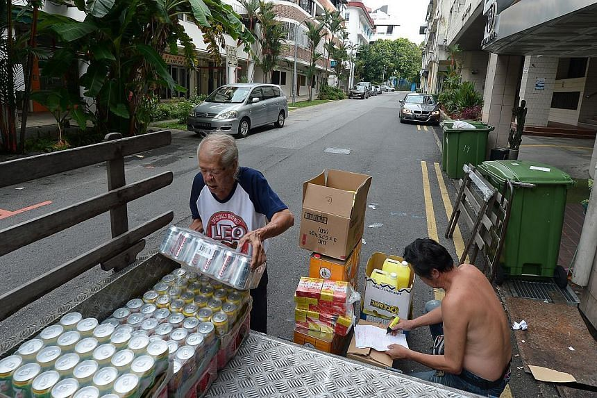 (Above)  At general supplies store Hock Leong Hin Teck Kee, Mr Lee Hon Fay (left), 75, and store owner Lee Sui Tiong, 65, load supplies for a client. -- ST PHOTO: NG SOR LUAN