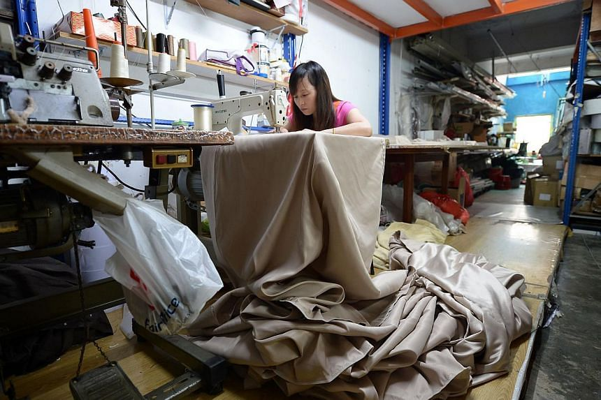 Seamstress Lu Mei Cui, 37, working on a set of curtains at her boss' shop, Sin Yick Seng Bamboo Chick Centre, a blinds and curtains maker.