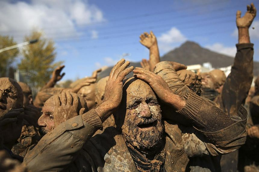Iranian Shi'ites cover themselves with mud, during Ashoura, marking the death anniversary of Imam Hussein, the grandson of Islam's Prophet Muhammad, at the city of Bijar, west of the capital Teheran, Iran on Thursday, Nov 14, 2013. Hussein, one