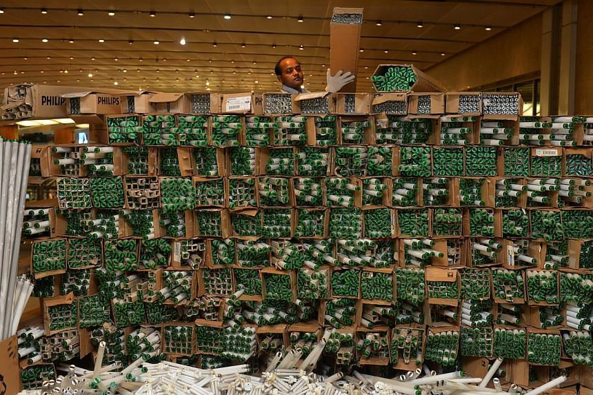 Technician Md Yousuf Sardar Abdul Khalek, 29, stacking boxes of used fluorescent light bulbs together at Changi Terminal 2 on Friday, Nov 15, 2013. Stacks of folded cardboard boxes, computers, and even a microwave oven lay on the floor at t