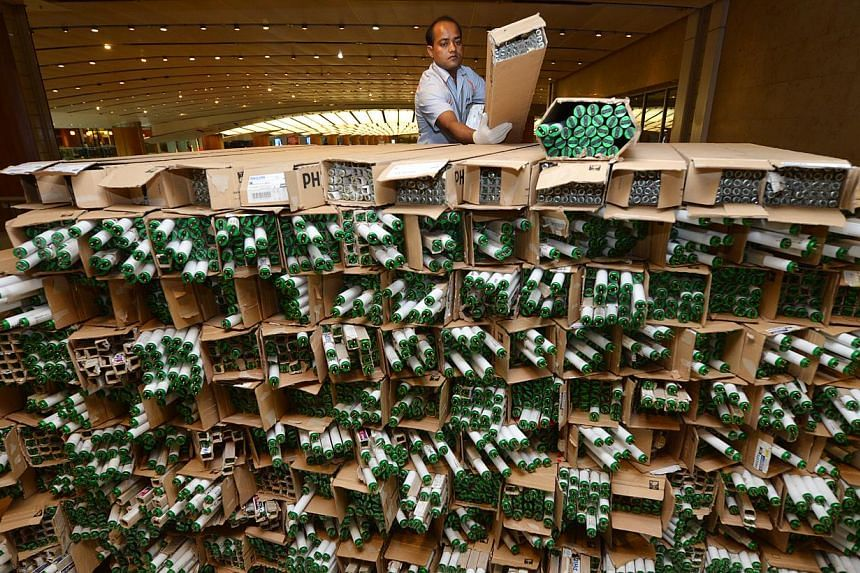 Technician Md Yousuf Sardar Abdul Khalek, 29, stacking boxes of used fluorescent light bulbs together at Changi Terminal 2 on Friday, Nov 15, 2013. -- ST PHOTO: CAROLINE CHIA