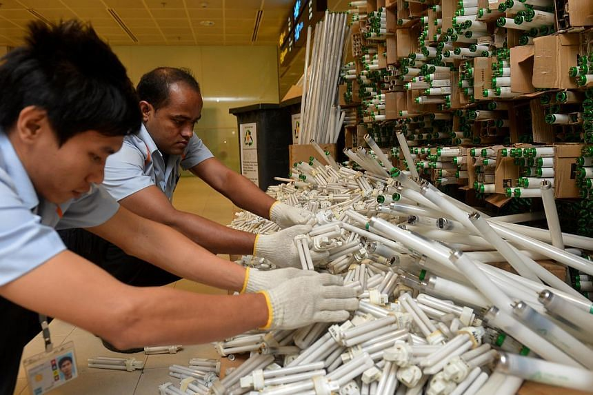 (From left) Technicians Aung Bo Bo Htwe, 26, and Md Yousuf Sardar Abdul Khalek, 29, stacking used light bulbs together at Changi Terminal 2on Friday, Nov 15, 2013.-- ST PHOTO:CAROLINE CHIA