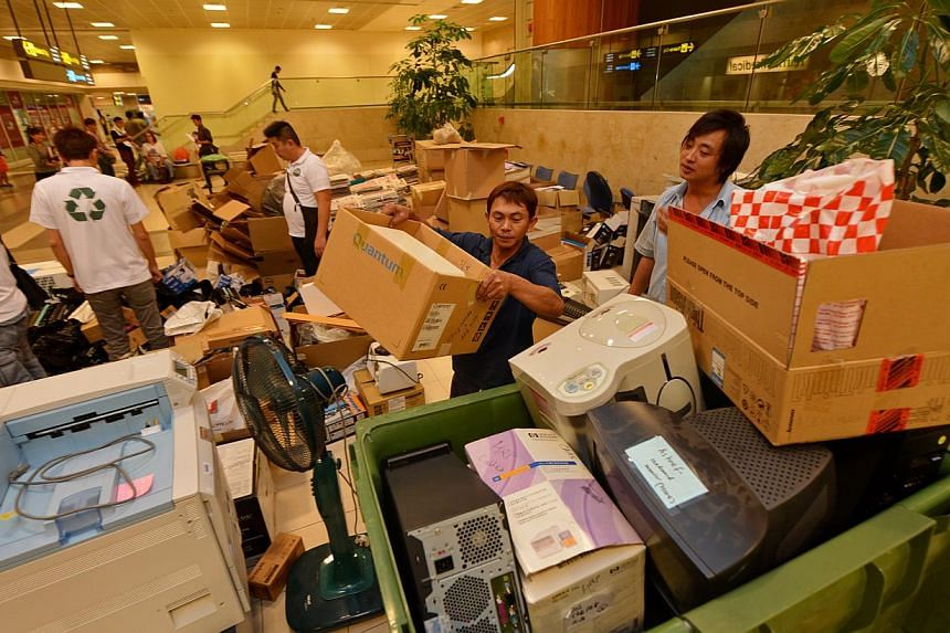 Mr Juing Anak Bandak (centre, in dark blue top), 36, and Mr Tian Xin (right, in light blue top), 27, from Chiang Kiong, a recycling company, collecting the e-waste collected at Changi airport,on Friday, Nov 15, 2013. -- ST PHOTO:CAROLINE