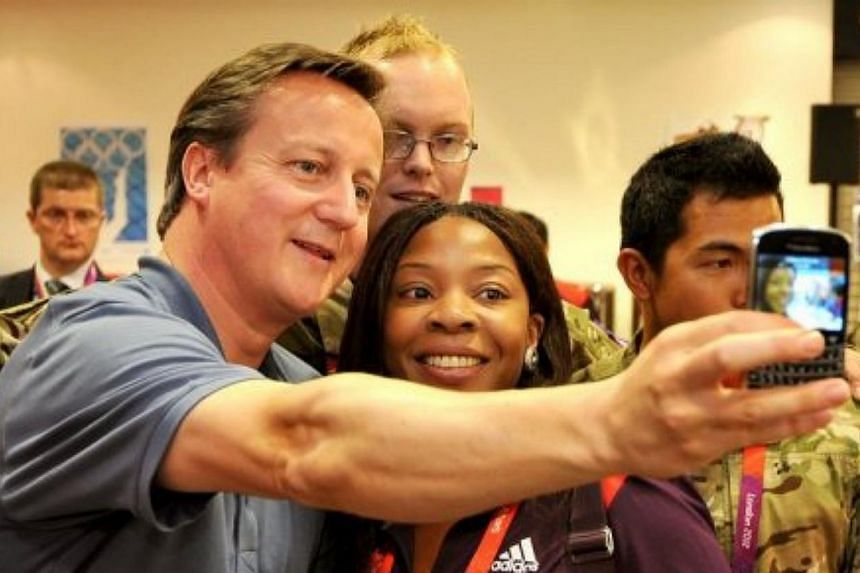 British Prime Minister David Cameron takes a selfie with with Olympic volunteer Anita Akuwudike in London in August 2012. -- PHOTO: AFP