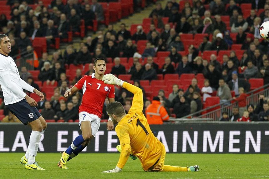 Chile's forward Alexis Sanchez (centre) scores his second goal beating England's goalkeeper Fraser Forster (right) during the international friendly football match between England and Chile at Wembley in north London on Nov 15, 2013.England's W