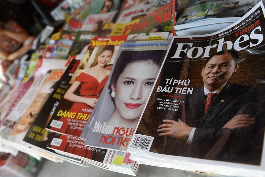 A copy of the newly launched Vietnamese version of Forbes Magazine is seen on sale at a roadside newsstand in Hanoi in this June 26, 2013, file photo. Forbes Media, the family-owned group known for its business magazine which chronicles great wealth,