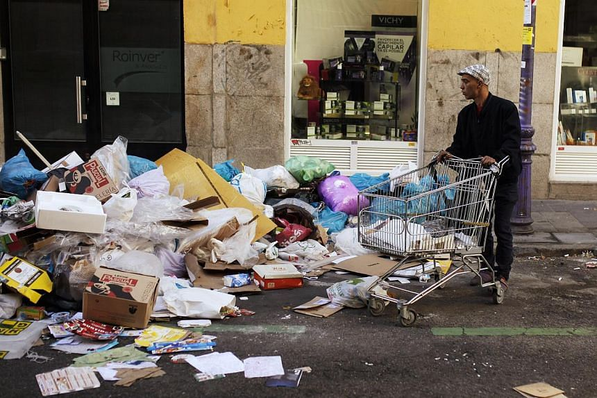 A man who collects garbage for a living looks at a pile of rubbish during the eleventh day of a garbage collectors strike, Madrid, Spain on Nov 15, 2013. Emergency workers with police escorts will begin cleaning trash off the streets of Spain's capit