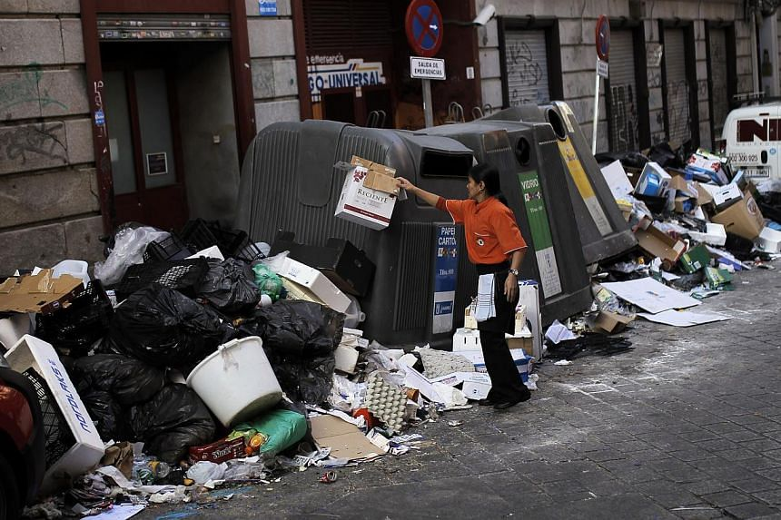 A woman throws a cardboard box on top of a pile of rubbish surrounding overflowing containers during the eleventh day of a garbage collectors strike, in Madrid, Spain, on Friday, Nov 15, 2013. Emergency workers with police escorts will begin cleaning
