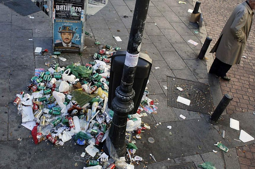 A man walks past garbage strewn on a pavement on the 11th day of an indefinite strike by street cleaners in Madrid on Nov 15, 2013. Emergency workers with police escorts will begin cleaning trash off the streets of Spain's capital on Saturday after s