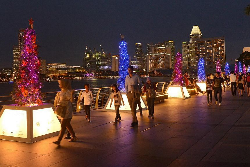 People walking along the Marina Bay Waterfront Promenade, which is illuminated by some 30 Christmas charity trees put up by the Community Chest and the Urban Redevelopment Authority. The trees, designed by students from Lasalle College of the Arts, h