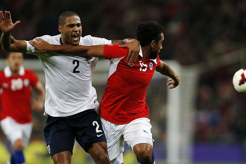 England's defender Glen Johnson (2nd left) vies for the ball against Chile's forward Jean Beausejour (right) during the international friendly football match between England and Chile at Wembley in north London on Nov 15, 2013. -- PHOTO: AFP