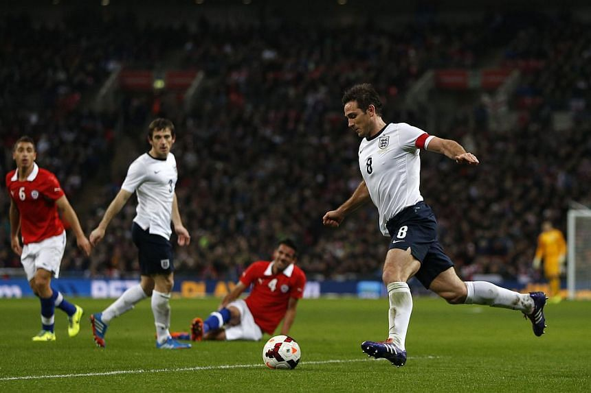 England's Frank Lampard (right) runs with the ball during the international friendly football match between England and Chile at Wembley in north London on Nov 15, 2013. -- PHOTO: AFP
