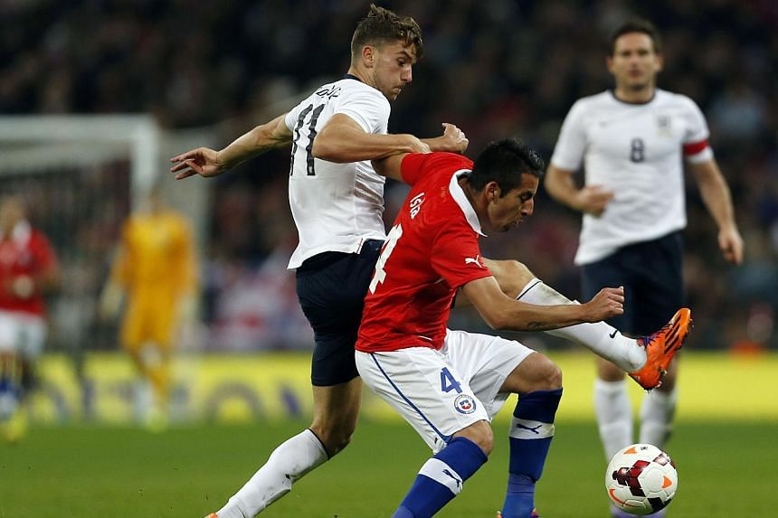 England's midfielder Jay Rodriguez (left) vies for the ball against Chile's defender Mauricio Isla (centre) during the international friendly football match between England and Chile at Wembley in north London on Nov 15, 2013. -- PHOTO: AFP