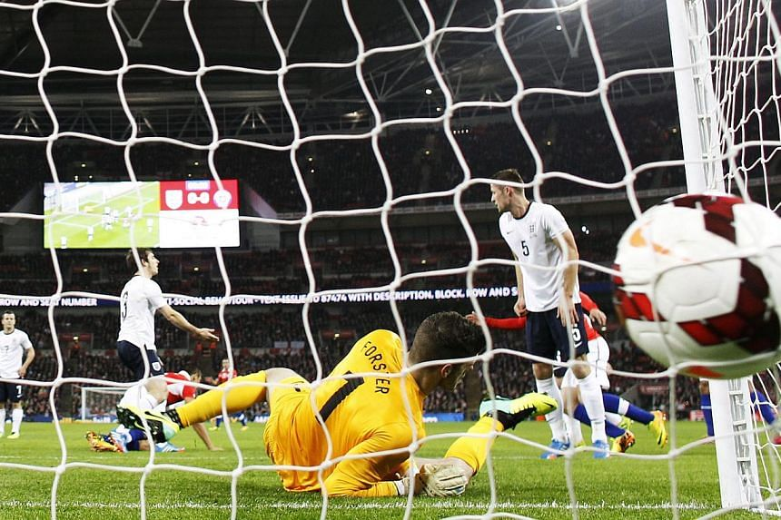 The ball hits the net as England's goalkeeper Fraser Forster dives across the goal during the international friendly football match between England and Chile at Wembley in north London on Nov 15, 2013. -- PHOTO: AFP