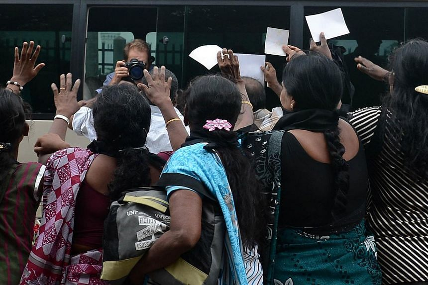 Sri Lankan ethnic Tamil women approach the media bus travelling with British Prime Minister David Cameron during a protest in Jaffna, some 400km north of Colombo on Nov 15, 2013. -- PHOTO: AFP