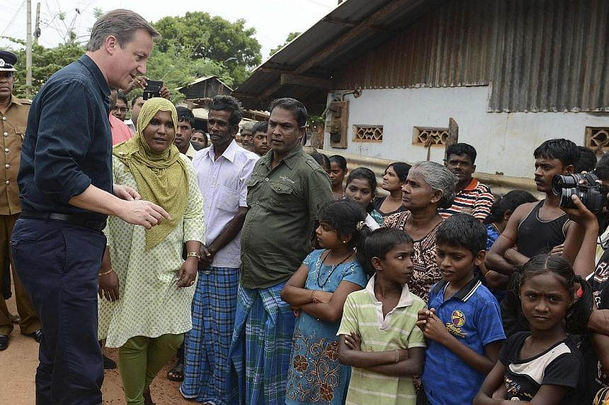 Britain's Prime Minister David Cameron (second, left), Chief Minister of Northern province, C. V. Vigneswaran (second, right) and Sri Lankan Tamil National Alliance (TNA) party leader R. Sampanthan (left) talk while looking out from the public librar