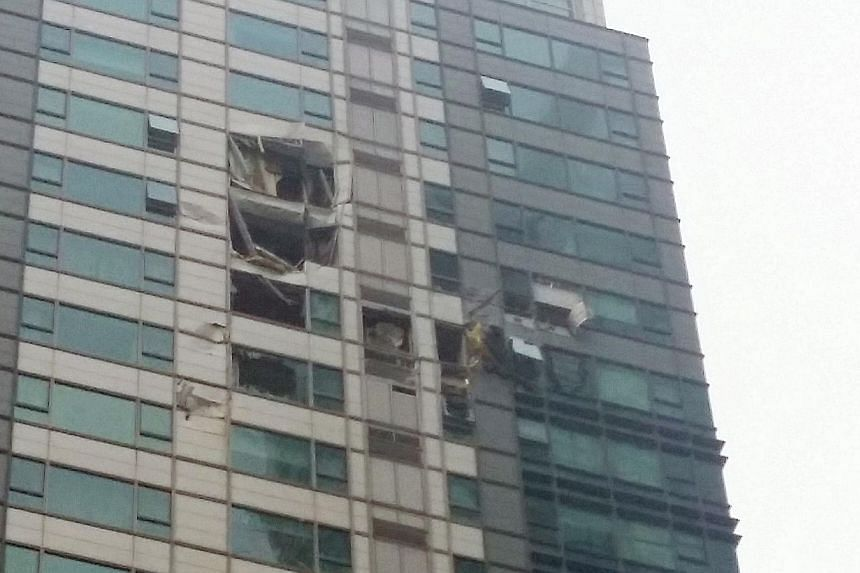 A damaged high-rise aparment is seen after a crash by a helicopter in Seoul's Gangnam district, on Nov 16, 2013. The private helicopter collided with several homes near the top of the 30-story apartment building before plunging to the ground. -- PHOT