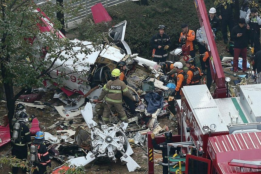 South Korean rescue workers search the wreckage of a helicopter after it crashed into a high-rise apartment leaving two pilots dead in Seoul's Gangnam district, on Nov 16, 2013. The private helicopter collided with several homes near the top of the 3