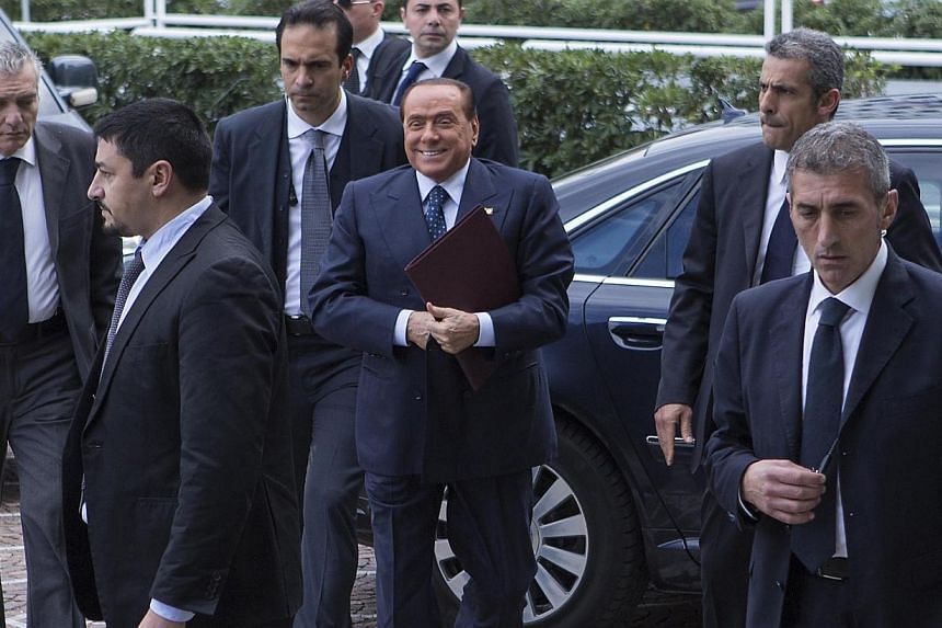 Forza Italia(Go Italy) Party founder Silvio Berlusconi, (centre) is surrounded by his body guards as he arrives at the Palazzo dei Congressi (Congress Palace) for the re-launch of his Forza Italia Party, in Rome, on Saturday, Nov 16, 2013.Mr Be
