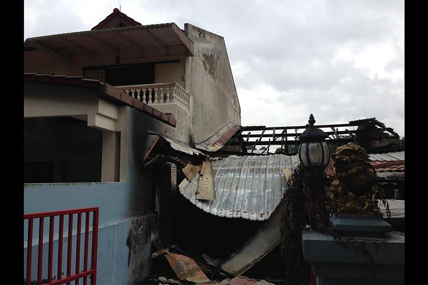 The burnt house and the neighbour's two-storey house (42 Jalan Gaharu) with charred walls on the left. -- ST PHOTO: YEO SAM JO