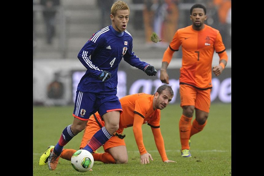 Japan midfielder Keisuke Honda (left) fights for the ball with Dutch midfielder Rafael van der Vaart (right) on Nov 16, 2013 during a World Cup 2014 friendly football match at the Cristal Arena in Genk. -- PHOTO: AFP