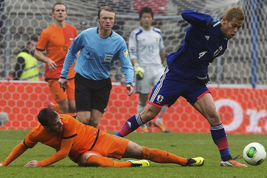 Japan midfielder Keisuke Honda (left) fights for the ball with Dutch forward Siem de Jongq (right) on Nov 16, 2013 during a World Cup 2014 friendly football match at the Cristal Arena in Genk. -- PHOTO: AFP