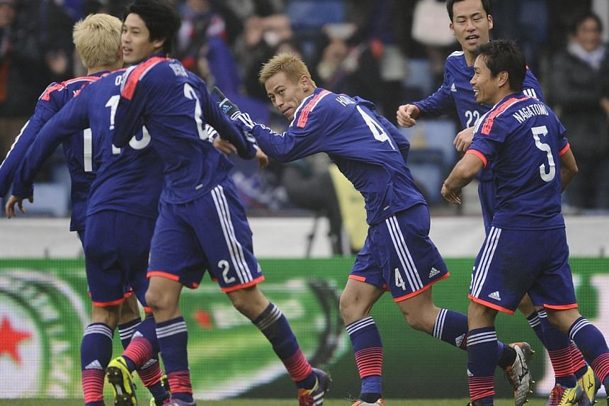 Japan midfielder Keisuke Honda (centre) celebrates after scoring against the Netherlands on Nov 16, 2013 during a World Cup 2014 friendly football match at the Cristal Arena in Genk. -- PHOTO: AFP