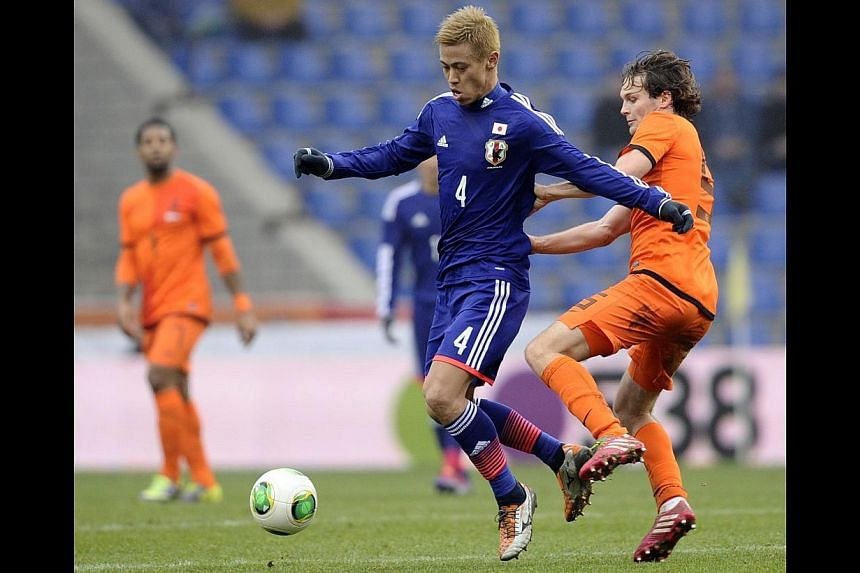Japan's Keisuke Honda (right) fights for the ball with Rafael van der Vaart of the Netherlands during their international friendly soccer match in Genk on Nov 16, 2013. -- PHOTO: REUTERS
