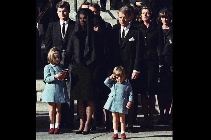 In this Monday, Nov 25, 1963 file photo, 3-year-old John F. Kennedy Jr. salutes his father's casket in Washington, three days after the president was assassinated in Dallas. Widow Jacqueline Kennedy (centre) and daughter Caroline Kennedy are accompan