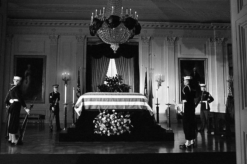 In this Saturday, Nov 23, 1963 file photo, President John F. Kennedy's flag-draped casket rests on a catafalque in the center of the East Room of the White House in Washington. -- FILE PHOTO: AP
