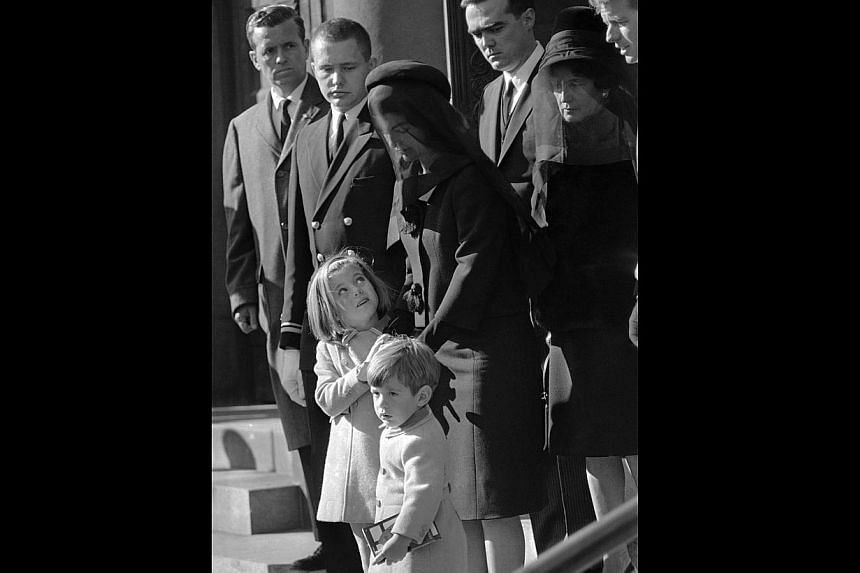 In this Monday, Nov 25, 1963 file photo, Caroline Kennedy, 5, looks to her mother, Jacqueline Kennedy, as she clutches her hand, accompanied by John F. Kennedy, Jr, 3, while leaving St. Matthew's Cathedral after the funeral Mass for President John F.
