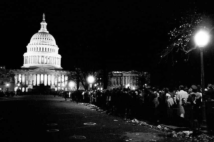 In this Sunday, Nov 24, 1963 file photo, mourners stand in a line which lasted through the night, to pay their respects to the slain President John F. Kennedy, in Washington, with the illuminated US Capitol in the background. -- FILE PHOTO: AP