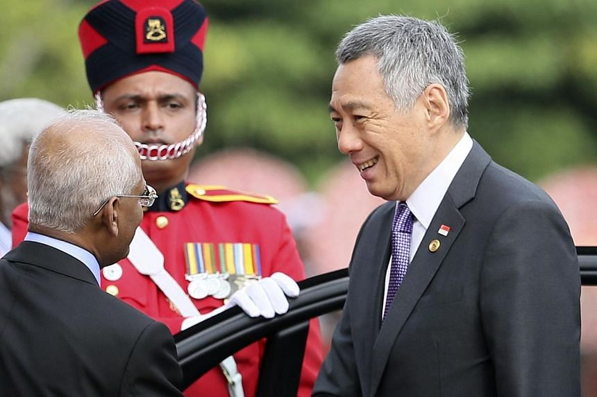 Prime Minister Lee Hsien Loong (right) shakes hands with Mr Lalith Weeratunga, secretary to Sri Lanka's President, as he arrives at the Commonwealth Heads of Government Meeting (CHOGM) opening ceremony in Colombo on Nov 15, 2013. Singapore is past th