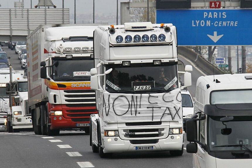 French truck drivers demonstrate against the Ecotax on the motorway outside Lyon, on Nov 16, 2013. Thousands of trucks blocked motorways across France on Saturday in protest at the government's controversial plans for an tax on heavy vehicles, causin