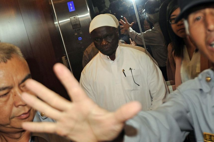 Policemen stop the press from taking photos of Gambia Ambassador to Taiwan Alhaji Ebrima N.H. Jarjou (centre) at the Foreign Ministry in Taipei, on Friday, Nov 15, 2013.Taiwan has sent senior diplomats to Gambia in a last-ditch effort to restor