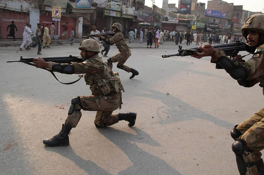 Pakistani army soldiers take position to disperse Sunni Muslims protesting against the attack on aSunni mosque and seminary, in Multan, on Saturday, Nov 16, 2013.Pakistan on Sunday ordered an inquiry into sectarian violence in the garrison city
