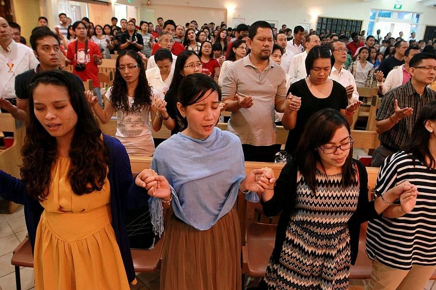 More than a thousand Filipinos gathered at St Vincent de Paul church this afternoon for a special mass organised by parish priest Father Michael Sitaram. -- ST PHOTO: NEO XIAOBIN