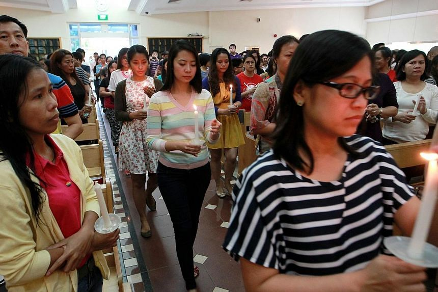 More than a thousand Filipinos hold lit candles in solidarity as they gathered at St Vincent de Paul church this afternoon for a special mass organised by parish priest Father Michael Sitaram. -- ST PHOTO: NEO XIAOBIN