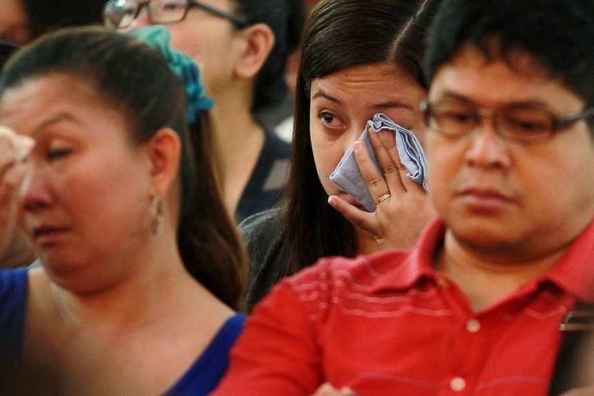 Church goers react during the testimonial of Ms Jaren D Loyola whose family back in the Philippines was affected when the typhoon hit.-- ST PHOTO:NEO XIAOBIN