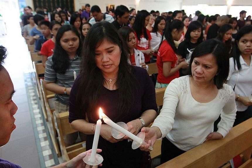 More than a thousand Filipinoshold lit candles in solidarity as theygathered at St Vincent de Paul church this afternoon for a special mass organised by parish priest Father Michael Sitaram. -- ST PHOTO:NEO XIAOBIN