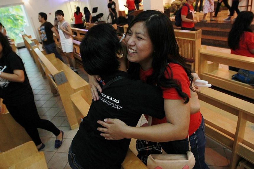 A friend gives Ms Jaren D Loyola a hug after her testimonial in church that recounts the ordeal of her family back in the Philippines was affected when the typhoon hit. -- ST PHOTO: NEO XIAOBIN