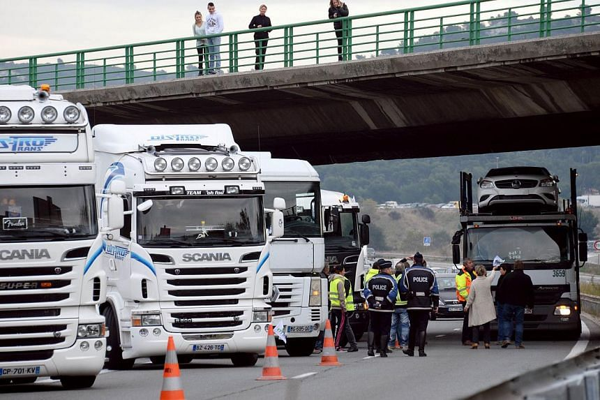 Truck drivers block a part of the highway A7 in Les Pennes-Mirabeau, southern France, to protest against an environmental tax on Nov 16, 2013. -- PHOTO: AFP
