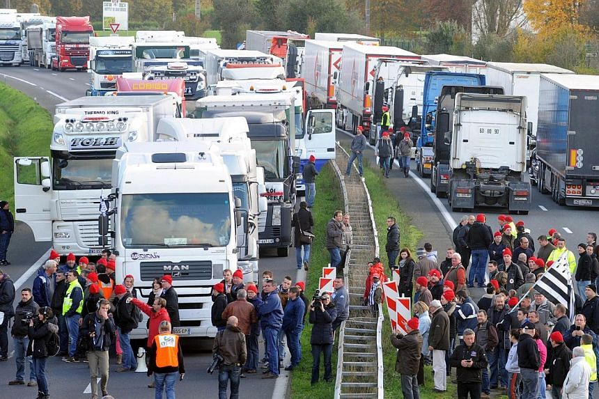 Truck drivers block a part of a highway near Lanrodec, western of France, to protest against an environmental tax on Nov 16, 2013. -- PHOTO: AFP