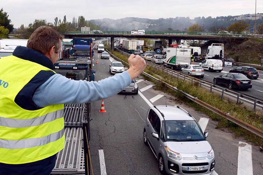 A truck driver raises his fist as takes part in a blocking of a part of the highway A7 in Les Pennes-Mirabeau, southern France, to protest against an environmental tax on Nov 16, 2013. -- PHOTO: AFP
