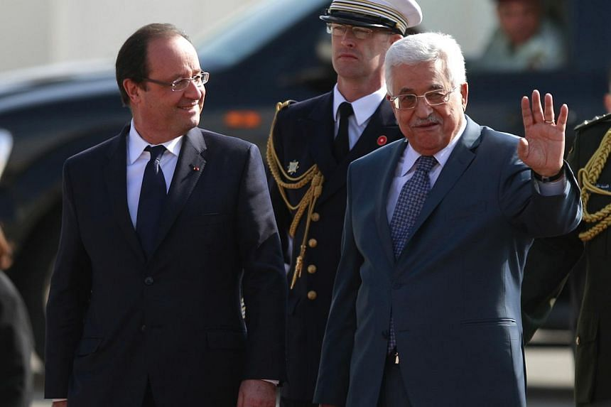 Palestinian President Mahmoud Abbas (right) waves as he and French President Francois Hollande walk past an honor guard during a welcoming ceremony in the West Bank city of Ramallah, Monday, Nov 18, 2013. Mr Hollande was meeting the Palestinian leade