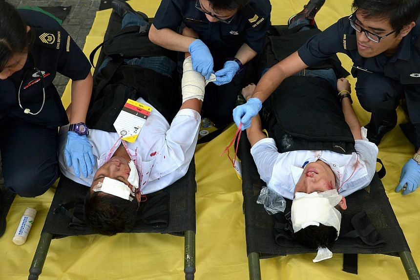 """""""Victims"""" of a suicide-bomber attack being attended to at the open plaza of the Singapore Land Tower in Shenton Way. -- ST PHOTO: KUA CHEE SIONG"""