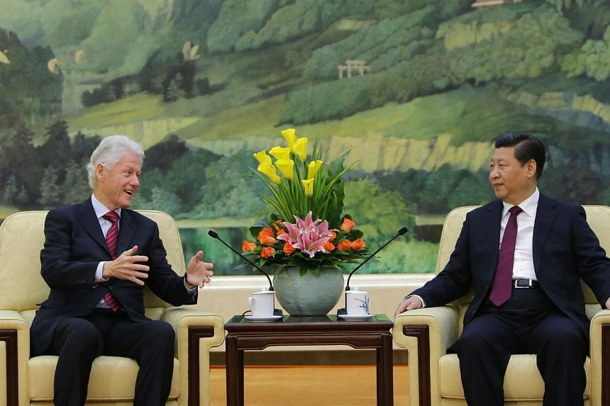 Former United State President Bill Clinton (left) speaks to China's President Xi Jinping during a meeting at the Great Hall of the People, in Beijing, Nov 18, 2013. Mr Clinton hopes there will be a woman in the White House in his lifetime, he told a
